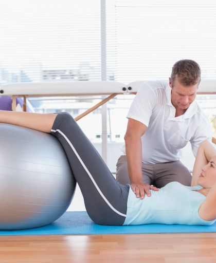 Woman lying on her back with a physiotherapist holding her, whilst her legs are resting on a gray medicine ball