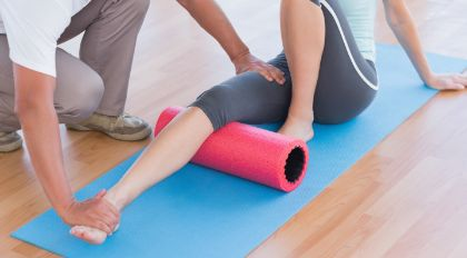 Woman with a foam roller under her knee, with a physiotherapist holding her leg down